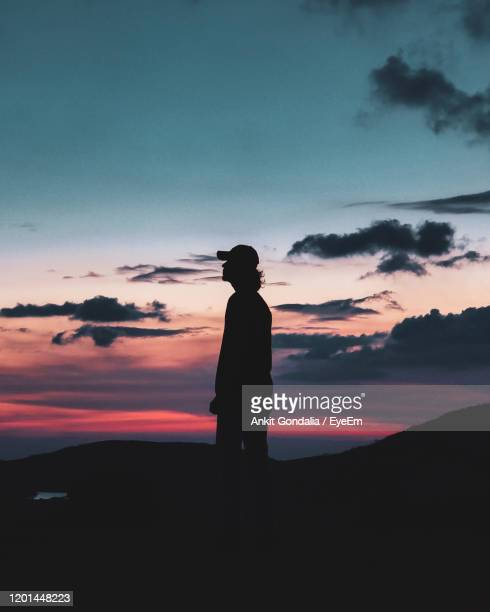 silhouette man standing against sky during sunset - 25 29歳 ストックフォトと画像