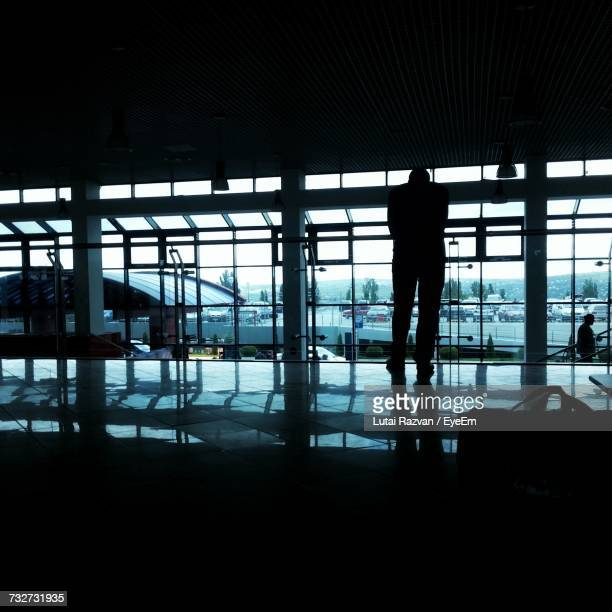 silhouette man standing at airport - lutai razvan stock pictures, royalty-free photos & images
