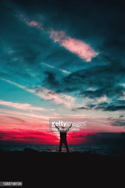 Silhouette Man Standing At Beach Against Cloudy Sky During Sunset