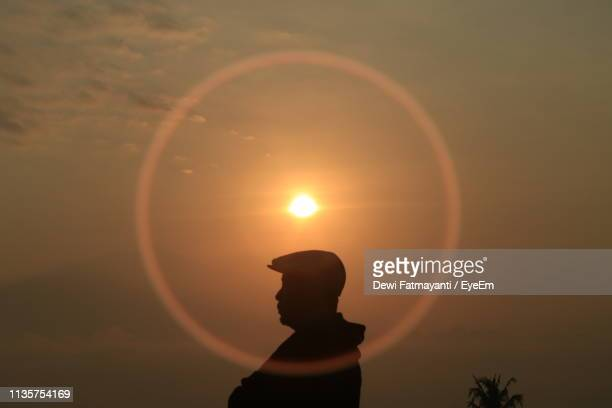 silhouette man standing at sundog against sky during sunset - dewi fatmayanti stock photos and pictures