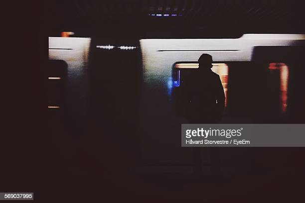 Silhouette Man Standing In Front Of Train At Subway Station