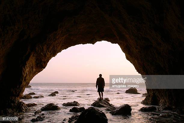 silhouette man standing in sea cave at sunset - malibu beach stock pictures, royalty-free photos & images