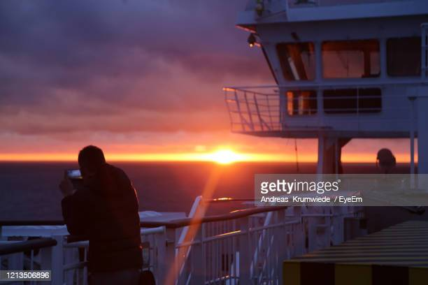 silhouette man standing on balcony against sea during sunset - andreas solar stock pictures, royalty-free photos & images