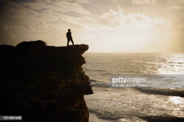 silhouette man standing on cliff near sea against sky during sunset - falaise photos et images de collection