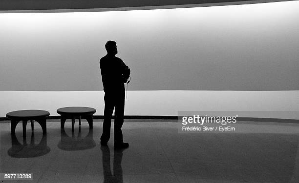 silhouette man standing on floor against wall - solomon r. guggenheim museum stock photos and pictures
