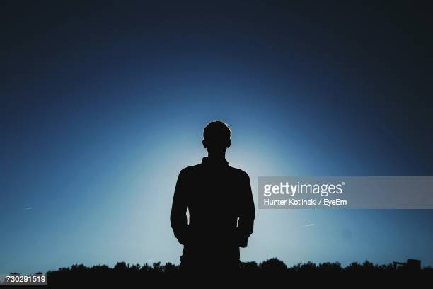silhouette man standing on grassy field against clear blue sky - one teenage boy only stock pictures, royalty-free photos & images