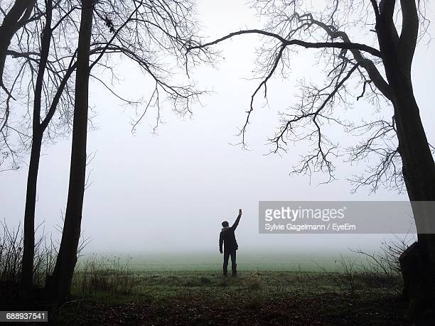 Silhouette Man Standing On Grassy Field Against Sky During Foggy Weather