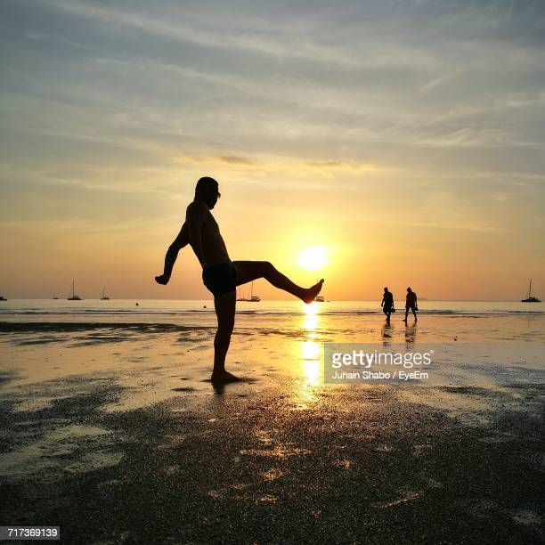 Silhouette Man Standing On Leg At Beach Against Sky During Sunset