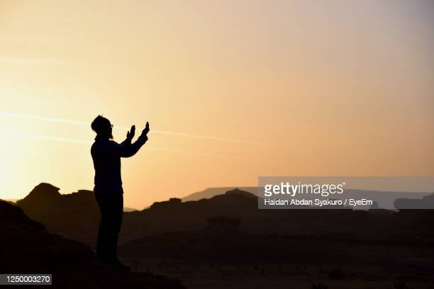 silhouette man standing on mountain against sky during sunset - islam stock pictures, royalty-free photos & images