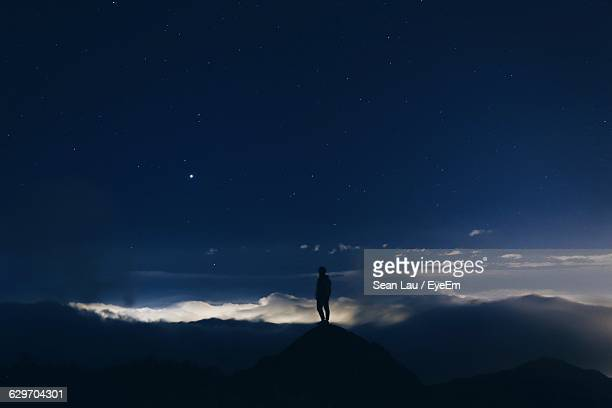 Silhouette Man Standing On Mountain Peak Against Sky At Night