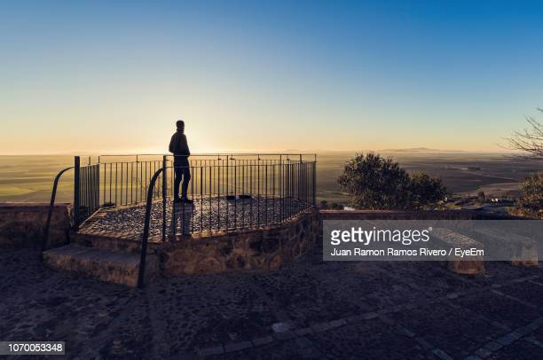 Silhouette Man Standing On Observation Point Against Clear Sky During Sunset