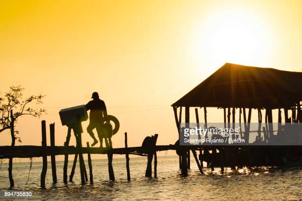 Silhouette Man Standing On Pier Against Clear Sky During Sunset