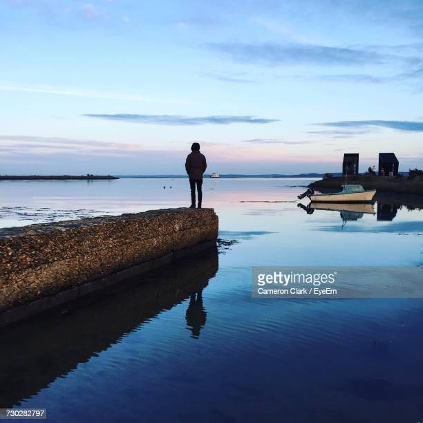 silhouette man standing on pier amidst lake against sky at dusk - lymington stock photos and pictures