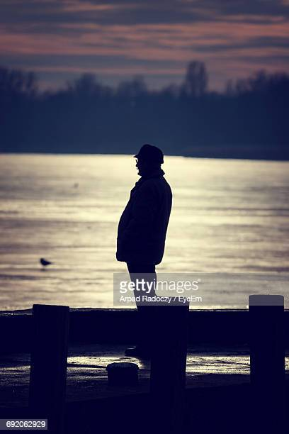 Silhouette Man Standing On Pier Over Lake Against Cloudy Sky During Sunset