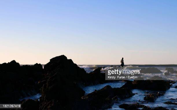 silhouette man standing on rock by sea against clear sky during sunset - space mission stock pictures, royalty-free photos & images