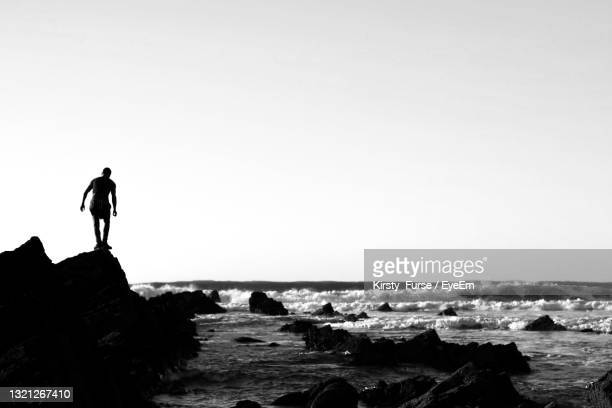 silhouette man standing on rock by sea against clear sky - space mission stock pictures, royalty-free photos & images