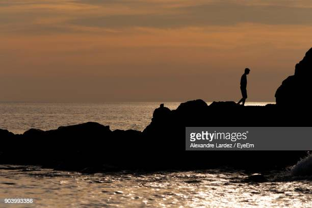 silhouette man standing on rock by sea against sky during sunset - alexandre coste foto e immagini stock