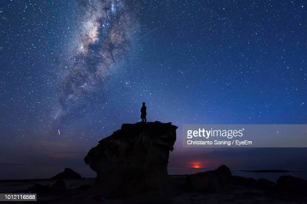 silhouette man standing on rock formation against star field at night - guardare in una direzione foto e immagini stock