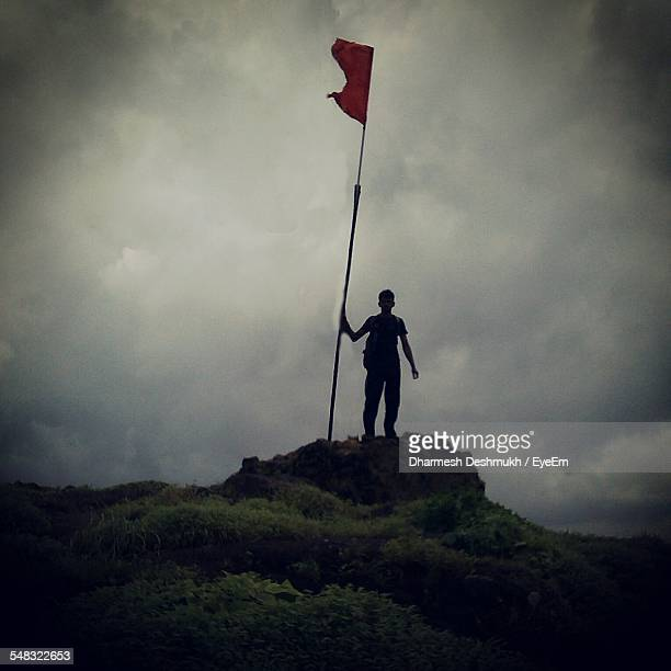 silhouette man standing on rocks against clouds - flagpole stock pictures, royalty-free photos & images