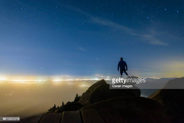 silhouette man standing on rocks against star field at mount pilchuck state park during night - cliff stock pictures, royalty-free photos & images