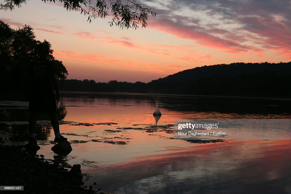 Silhouette Man Standing On Rocks At Shore During Sunset : Stock Photo