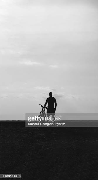 silhouette man standing with bicycle on field against sky - krasimir georgiev stock photos and pictures