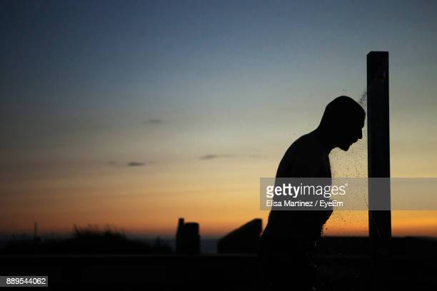 Silhouette Man Taking Shower At Beach Against Sky During Sunset