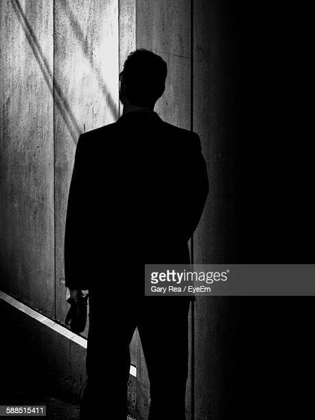 Silhouette Man Walking Against Wall At Night