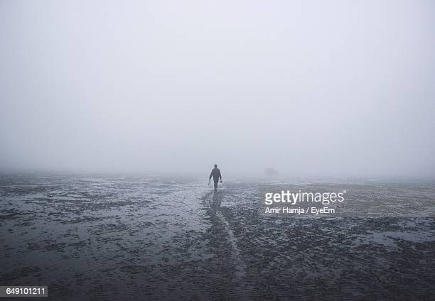 Silhouette Man Walking At Beach Against Clear Sky During Foggy Weather
