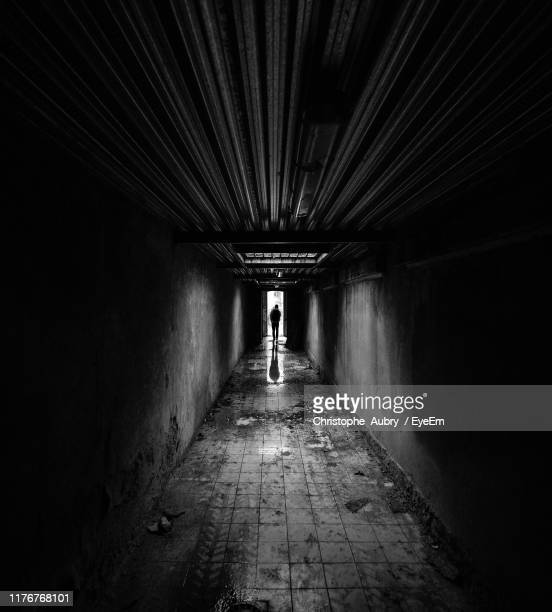 silhouette man walking in corridor - alley stock pictures, royalty-free photos & images