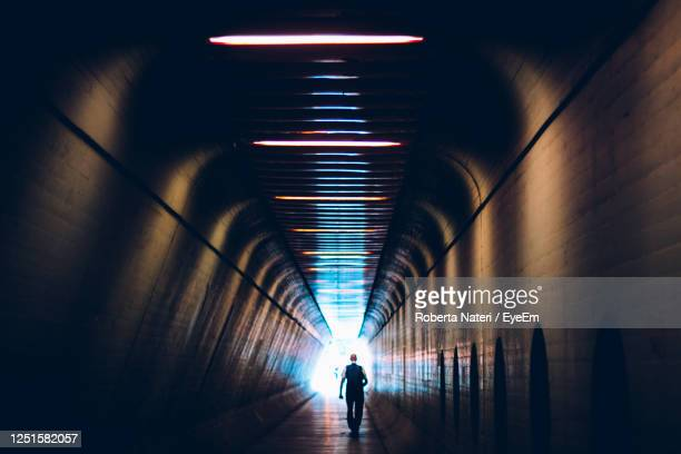 silhouette man walking in illuminated tunnel - public transport stock pictures, royalty-free photos & images
