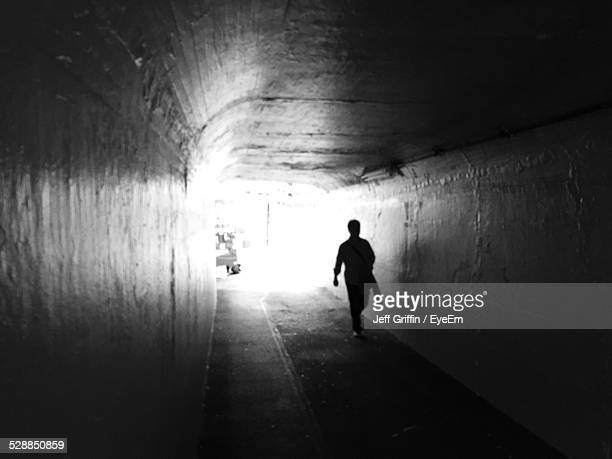 Silhouette Man Walking In Tunnel