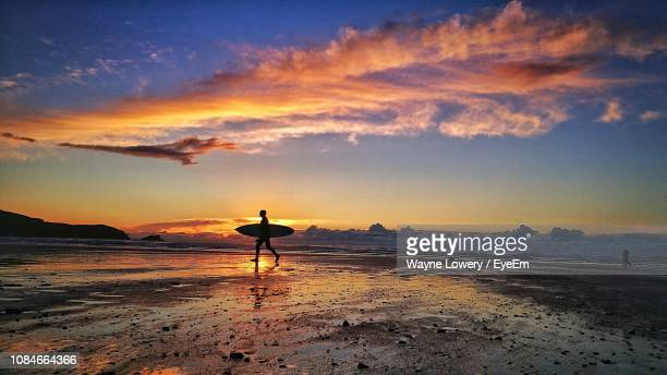 silhouette man walking on beach against sky during sunset - surf stock pictures, royalty-free photos & images