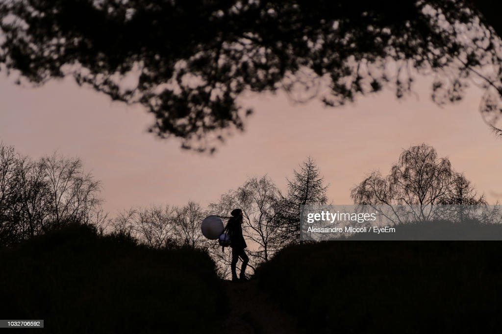 Silhouette Man Walking On Field Against Sky During Sunset : Stock Photo