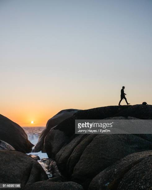 Silhouette Man Walking On Rock Against Sky During Sunset