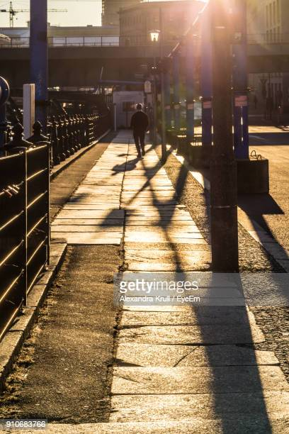 Silhouette Man Walking On Sidewalk In City During Sunny Day