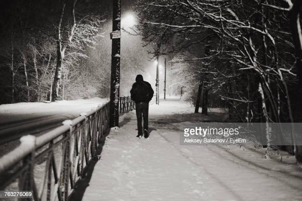 silhouette man walking on snow covered footpath - kaliningrad stock pictures, royalty-free photos & images