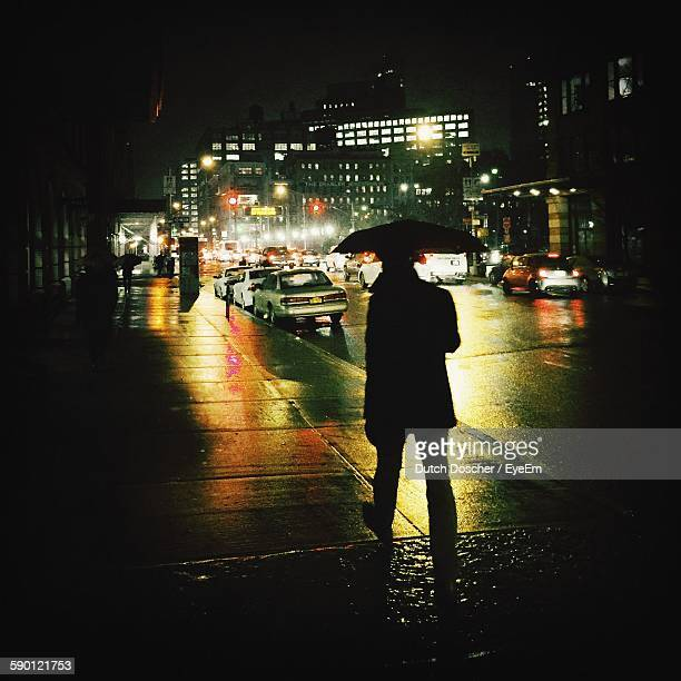 Silhouette Man Walking Under Umbrella On Wet Footpath In City At Night