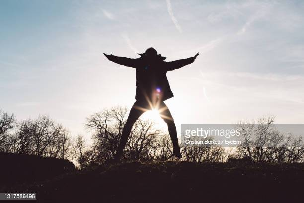 silhouette man with arms outstretched on field against sky - bortes stockfoto's en -beelden