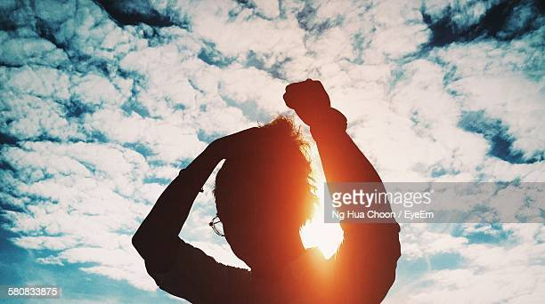 silhouette man with arms raised standing against cloudy sky - atheism stock photos and pictures