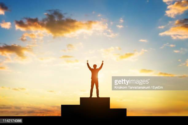 silhouette man with arms raised standing winners podium against sky during sunset - 達成 ストックフォトと画像