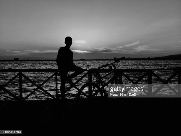 silhouette man with bicycle on promenade with sea in background against sky - cankaya district ankara stock pictures, royalty-free photos & images