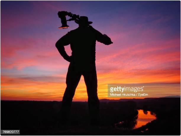 silhouette man with camera standing against orange sky - transferbild stock-fotos und bilder