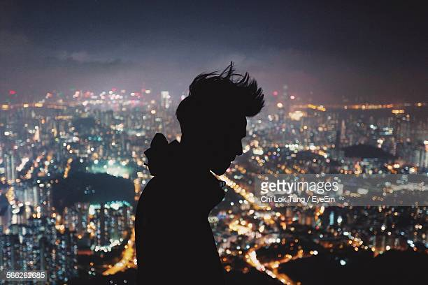 Silhouette Man With Illuminated Cityscape In Background At Night