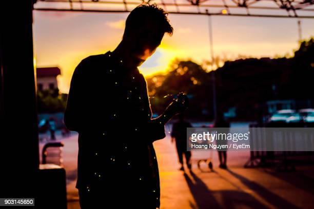 silhouette man with lighting equipment during sunset - 背景に人 ストックフォトと画像