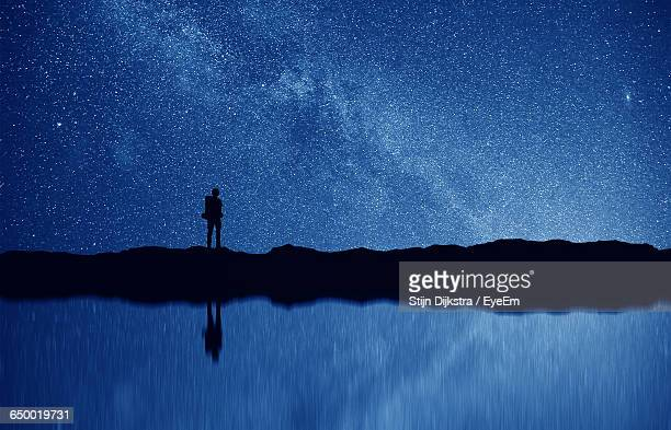 Silhouette Man With Reflection On Lake Against Star Field At Night