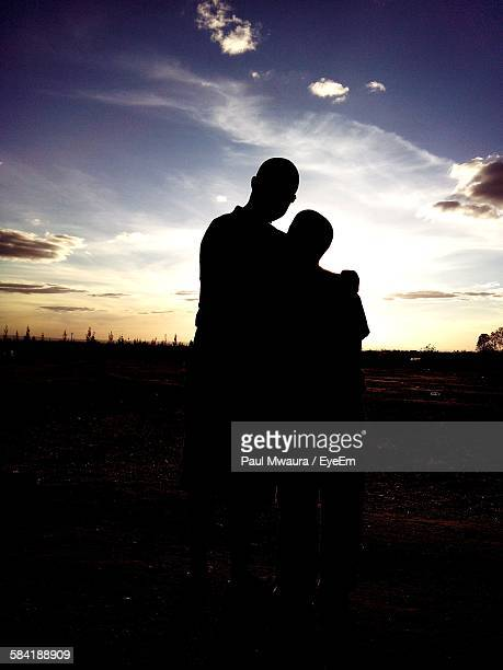 Silhouette Man With Son On Field Against Sky During Sunset