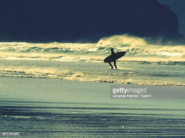 Silhouette Man With Surfboard In Sea Against Sky