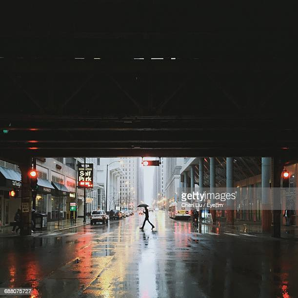 Silhouette Man With Umbrella Walking On City Street By Bridge During Monsoon