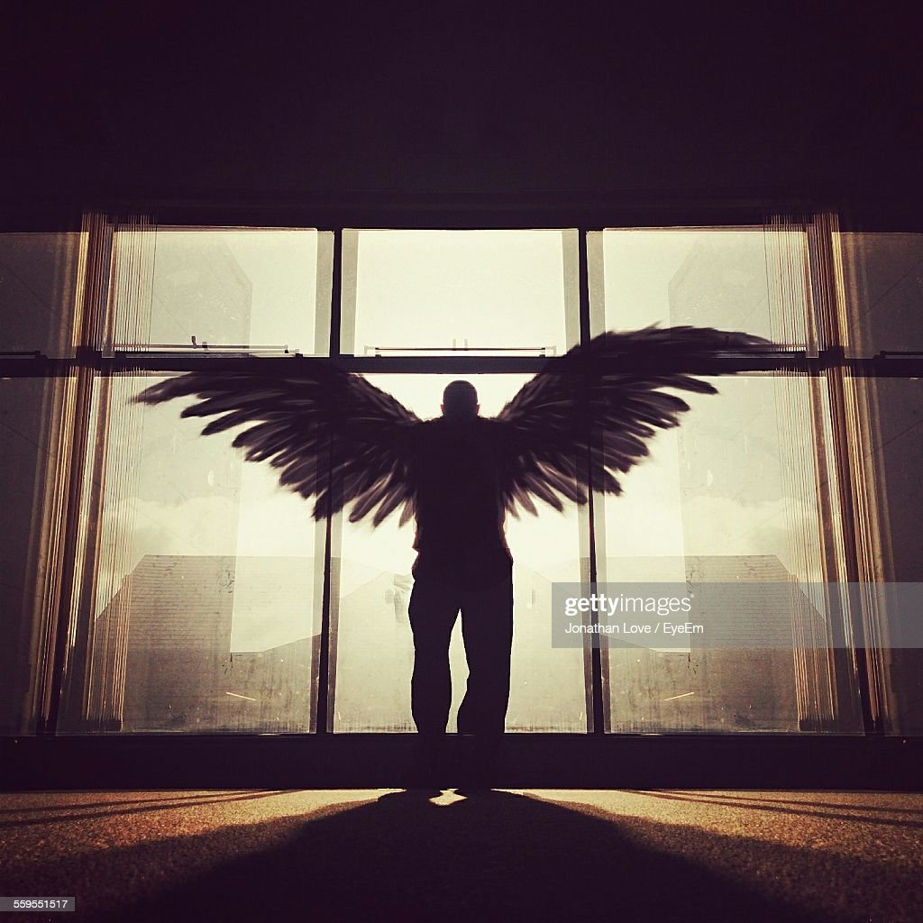 Silhouette Man With Wings Standing In Front Of Window : Stock Photo